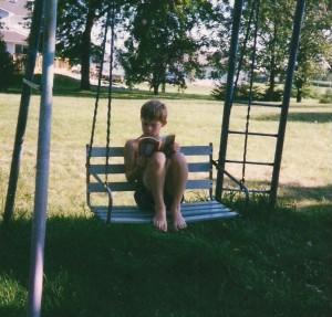 Shawn reading on swing